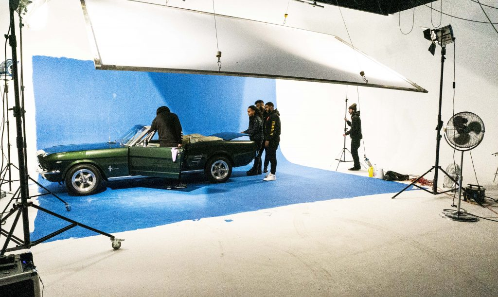 Scenery of a film production with a car in front of a blue painted cove