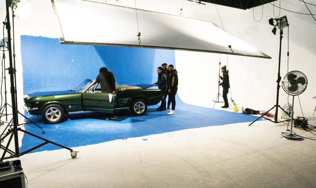 Kulisse einer Filmproduktion mit Auto vor einer blau gestrichenen Hohlkehle